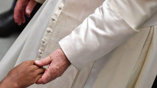 Paus Fransisku memegang tangan orang sakit
